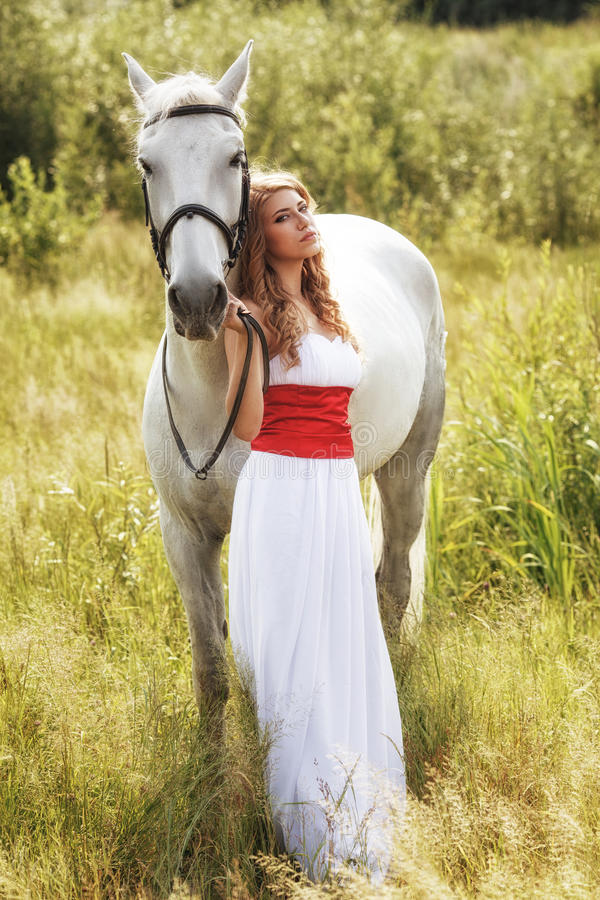 Όμορφες αισθησιακές γυναίκες με το άσπρο άλογο στοκ εικόνες