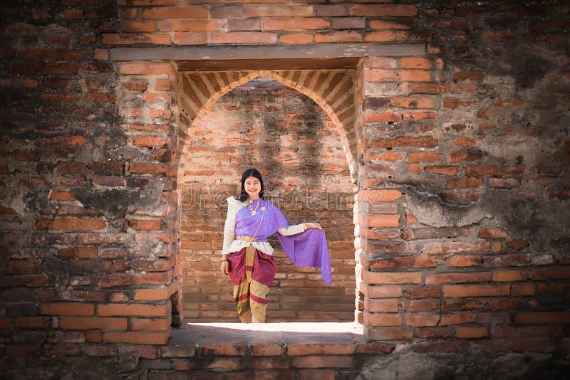 Όμορφες ασιατικές γυναίκες, ταϊλανδικοί λαοί που φορούν τα ταϊλανδικά ενδύματα, που στέκονται στον παλαιό τοίχο στοκ εικόνες