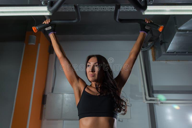 Όμορφες ασκήσεις κοριτσιών ικανότητας στον οριζόντιο φραγμό στην αθλητική γυμναστική, πίσω άποψη στοκ εικόνα