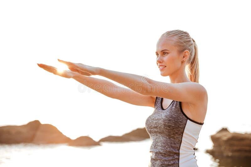 Όμορφες ασκήσεις χεριών γυναικών τεντώνοντας κατά τη διάρκεια της γιόγκας στην παραλία στοκ εικόνα με δικαίωμα ελεύθερης χρήσης