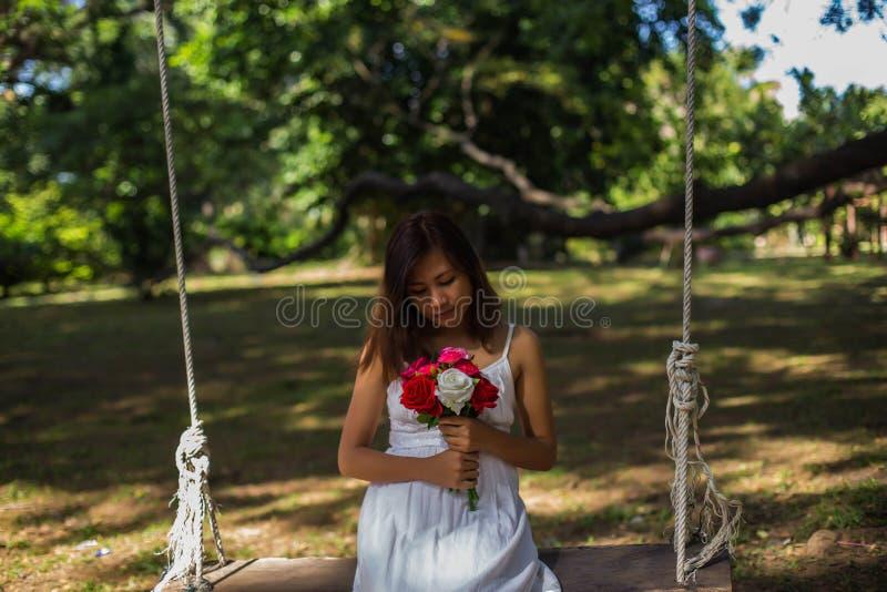 Όμορφες γυναίκες που κρατούν τα λουλούδια, που ταλαντεύονται κάτω από τα δέντρα στοκ φωτογραφίες