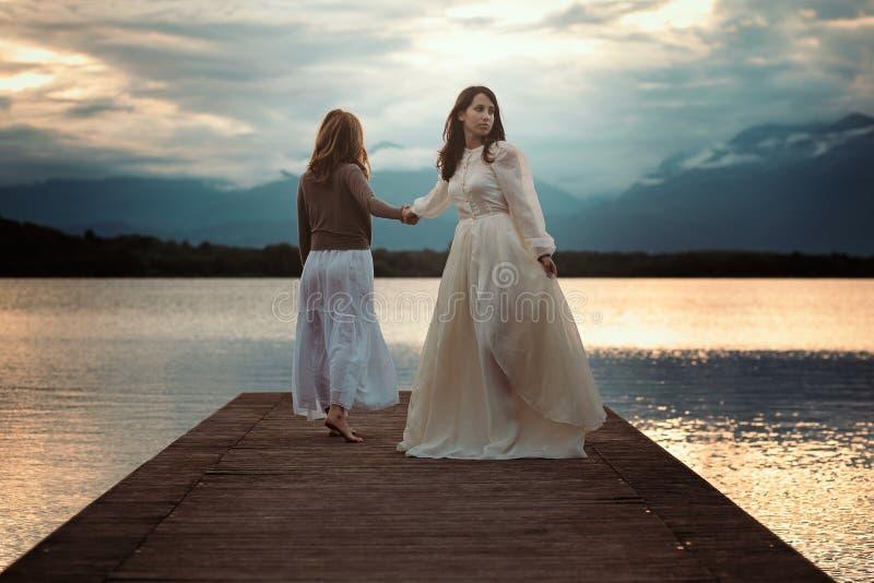 Όμορφες γυναίκες που περπατούν στην αποβάθρα λιμνών στοκ εικόνα