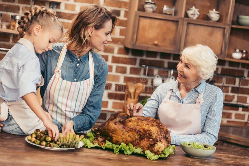 όμορφες γυναίκες τριών γενεών που προετοιμάζουν τα πιάτα στοκ φωτογραφία