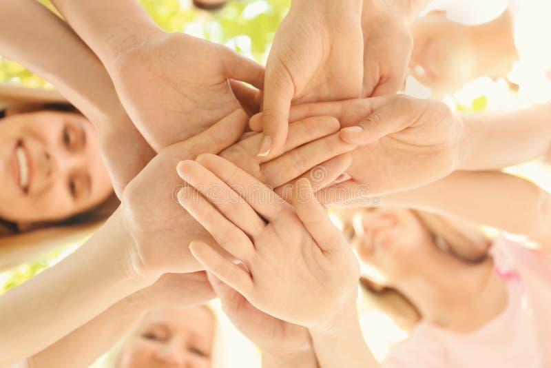 Όμορφες γυναίκες των διαφορετικών ηλικιών που βάζουν τα χέρια μαζί υπαίθρια, κινηματογράφηση σε πρώτο πλάνο Έννοια καρκίνου του μ στοκ φωτογραφία με δικαίωμα ελεύθερης χρήσης