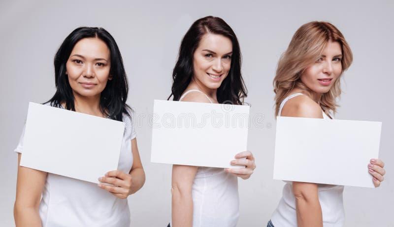 Όμορφες γυναίκες των διαφορετικών εθνών που καταδεικνύουν τα άσπρα σημάδια στοκ φωτογραφία