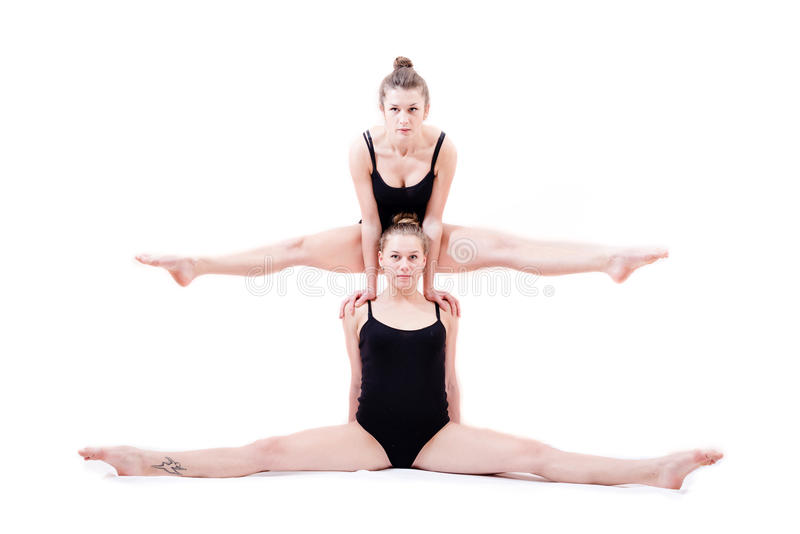 2 όμορφες εύκαμπτες νέες γυναίκες αθλητών που εγκαθιστούν στη διάσπαση μιας πάνω από τους ώμους άλλος στοκ φωτογραφία με δικαίωμα ελεύθερης χρήσης