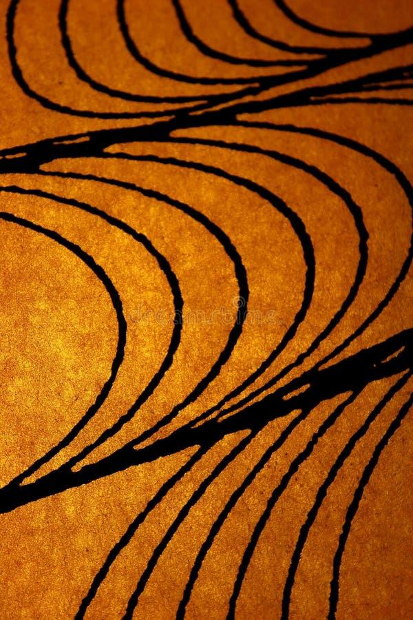 Όμορφες κατασκευασμένες μαύρες γραμμές στο χρυσό ελαφρύ υπόβαθρο στοκ εικόνα με δικαίωμα ελεύθερης χρήσης