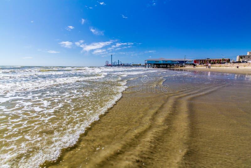 Όμορφες κυματωγή και άμμος σε μια ωκεάνια παραλία καλοκαιριού Με το λούνα παρκ καρναβάλι στοκ εικόνες