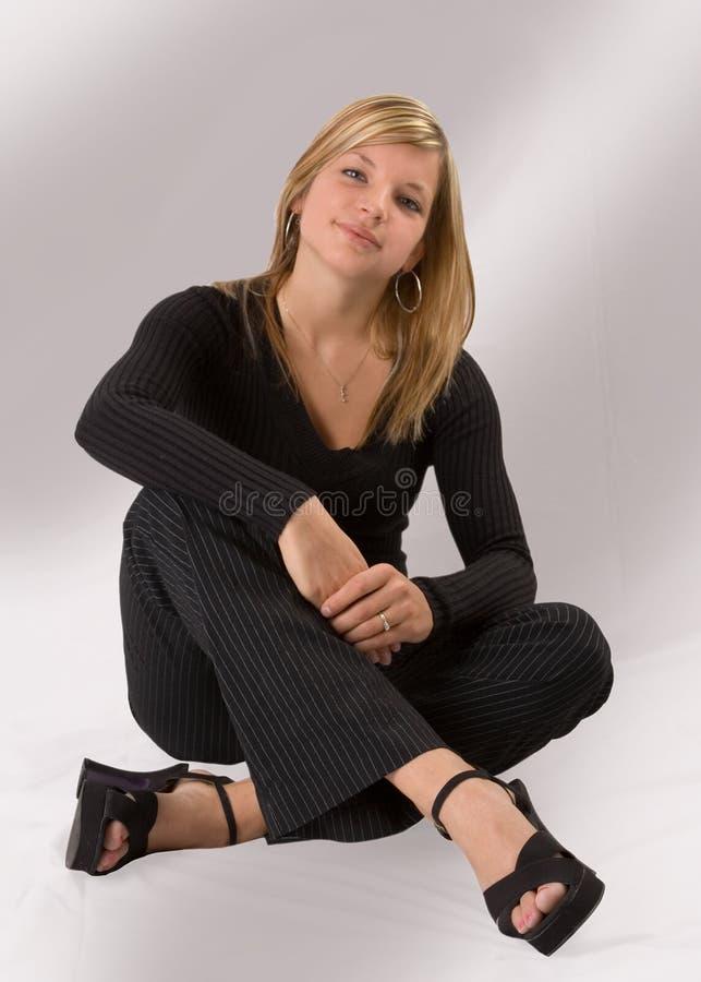 όμορφες μαύρες ξανθές νεολαίες γυναικών συνεδρίασης εξαρτήσεων στοκ φωτογραφία