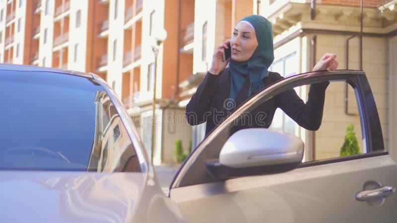 Όμορφες μουσουλμανικές στάσεις επιχειρησιακών γυναικών με το αυτοκίνητο με το τηλέφωνο στοκ φωτογραφίες