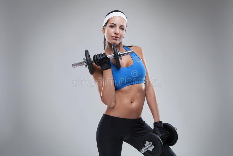 Όμορφες νέες jogging ασκήσεις γυναικών με τους αλτήρες που απομονώνονται στοκ φωτογραφία