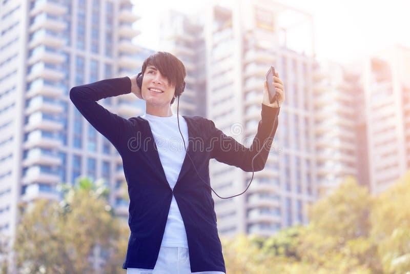 Όμορφες νεαρό χαμόγελο άνδρων και μουσική ακούσματος στην οδό Νεαρός άνδρας που ακούει τη μουσική σε ένα έξυπνο τηλέφωνο στοκ εικόνα