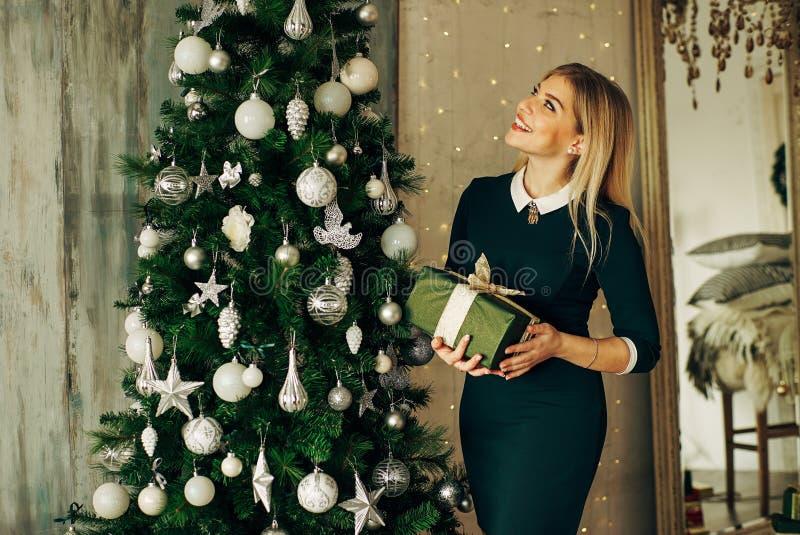 Όμορφες ξανθές στάσεις κοντά στο δέντρο και την εκμετάλλευση ένα δώρο στα χέρια στοκ φωτογραφία