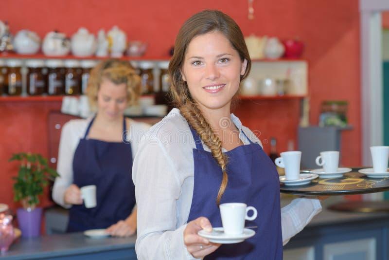 Όμορφες σερβιτόρες πίσω από το μετρητή που λειτουργεί στη καφετερία στοκ εικόνα