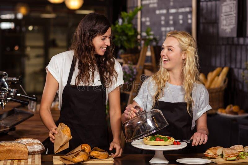 Όμορφες σερβιτόρες πίσω από το μετρητή στοκ εικόνα