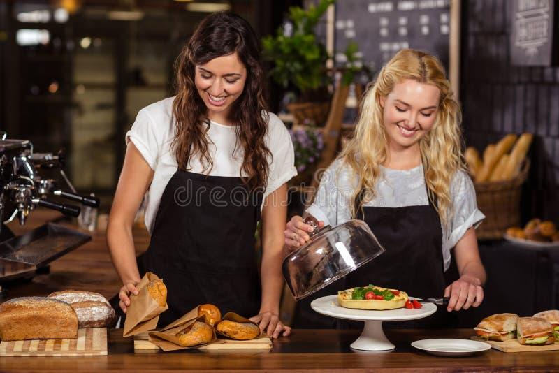 Όμορφες σερβιτόρες πίσω από το μετρητή στοκ φωτογραφία