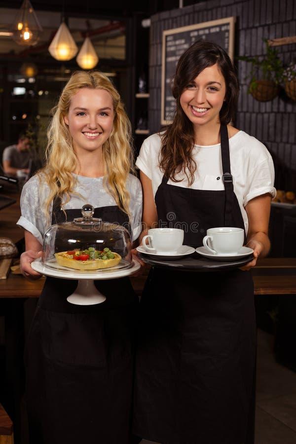 Όμορφες σερβιτόρες που θέτουν μπροστά από το μετρητή που παρουσιάζει τον καφέ και την πίτα στοκ εικόνα με δικαίωμα ελεύθερης χρήσης