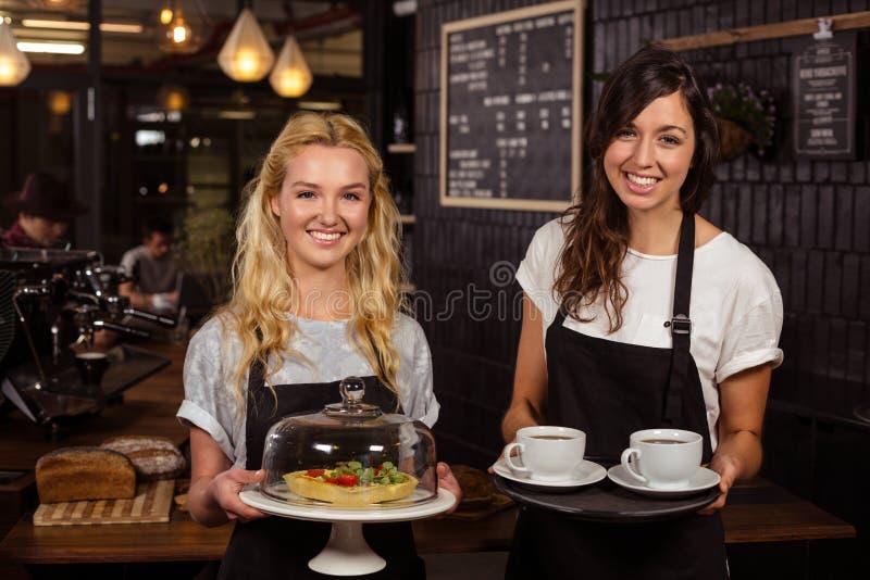 Όμορφες σερβιτόρες που θέτουν μπροστά από το μετρητή που παρουσιάζει τον καφέ και την πίτα στοκ εικόνες με δικαίωμα ελεύθερης χρήσης