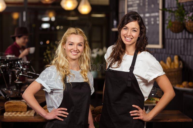 Όμορφες σερβιτόρες που θέτουν μπροστά από το μετρητή στοκ φωτογραφίες