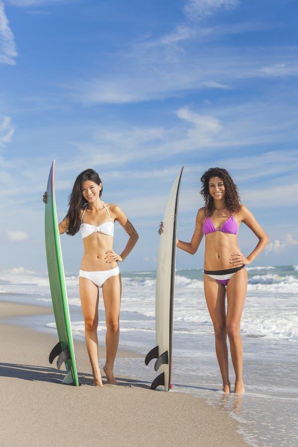 Όμορφες Bikini γυναίκες Surfers & ιστιοσανίδες στην παραλία στοκ εικόνα