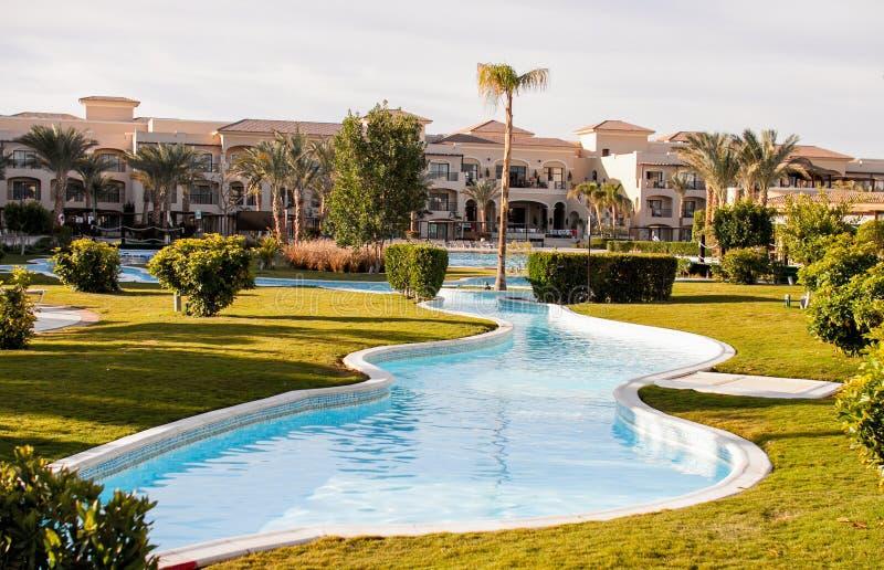 Όμορφη άποψη από την πισίνα ξενοδοχείων με τους φοίνικες στοκ εικόνα