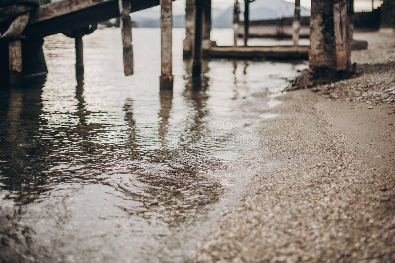 Όμορφη άποψη σχετικά με την παλαιά αποβάθρα και το νερό με τις πέτρες στην παραλία Lago Maggiore, πόλη Stresa, Ιταλία Αποβάθρα σε στοκ εικόνα με δικαίωμα ελεύθερης χρήσης