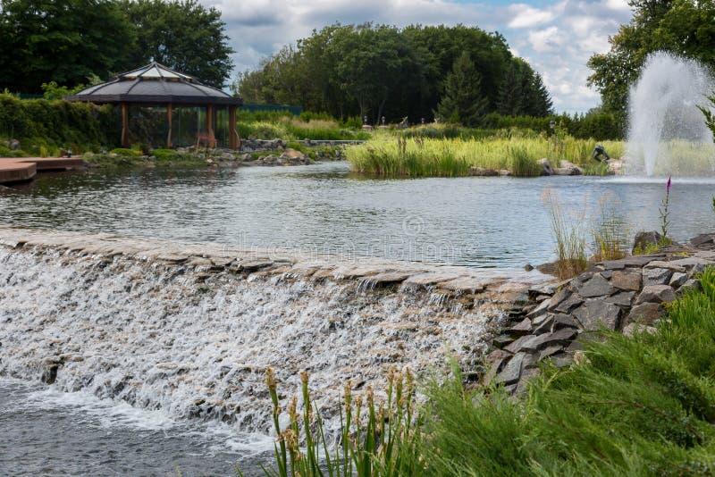 Όμορφη άποψη σχετικά με τον καταρράκτη του νερού που ρέει από τη λίμνη στο πάρκο στοκ φωτογραφία