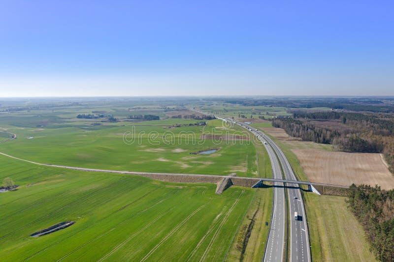 Όμορφη άποψη της εθνικής οδού με τα αυτοκίνητα πάνω από το υπόβαθρο των τομέων και των δασών στοκ εικόνες