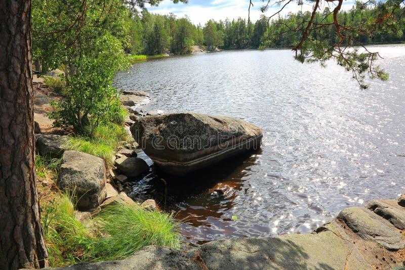 Όμορφη άποψη του μεγάλου βράχου στην γκρίζα επιφάνεια νερού ακτών λιμνών σε αντίθεση με τα πράσινα φύλλα των δέντρων στοκ φωτογραφίες με δικαίωμα ελεύθερης χρήσης