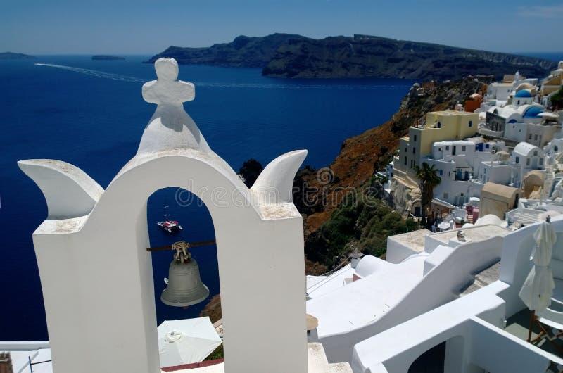 Όμορφη άποψη Oia με έναν πύργο κουδουνιών στο πρώτο πλάνο στοκ φωτογραφία