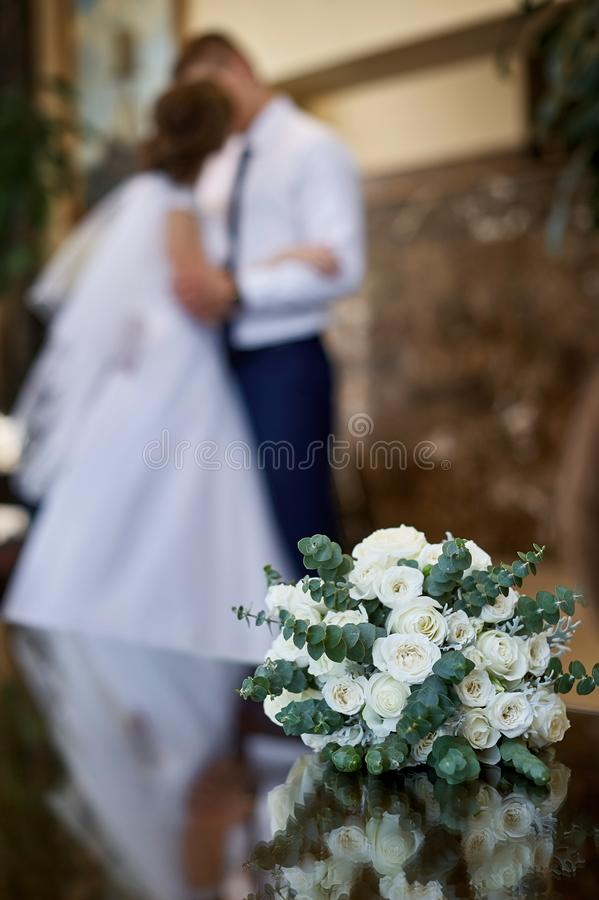 Όμορφη άσπρη γαμήλια νυφική ανθοδέσμη και στο φιλί υποβάθρου η νύφη και ο νεόνυμφος στοκ εικόνες