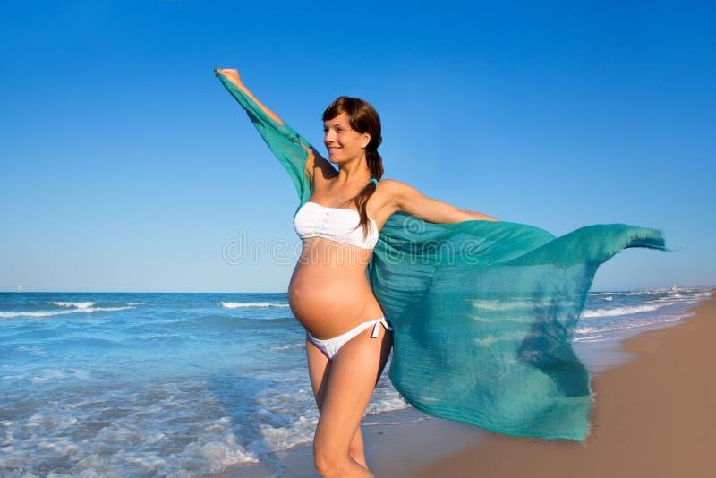Όμορφη έγκυος γυναίκα που περπατά στην μπλε παραλία στοκ εικόνες