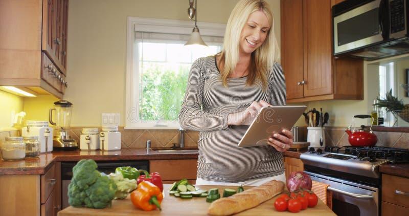 Όμορφη έγκυος γυναίκα που χρησιμοποιεί την ταμπλέτα στην κουζίνα στοκ εικόνα