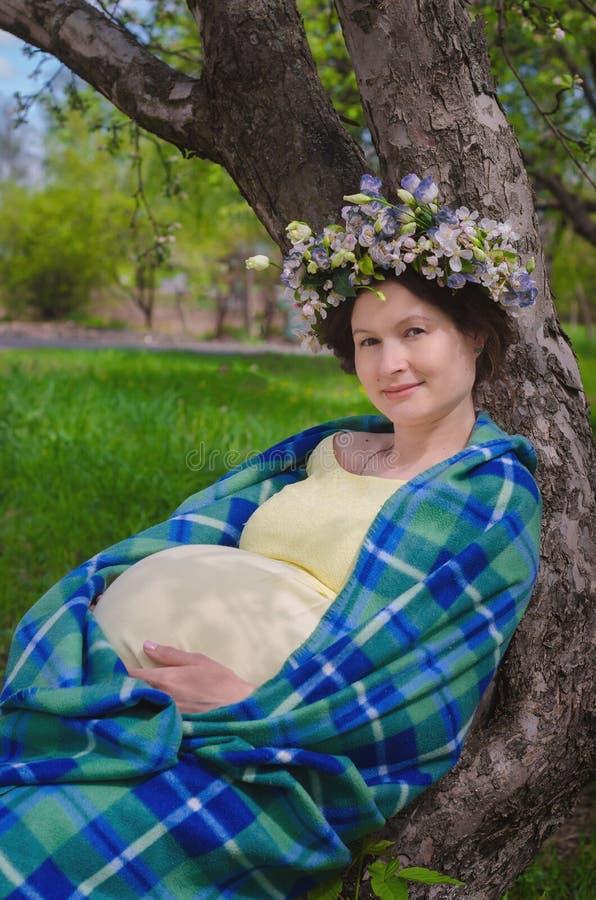 Όμορφη έγκυος γυναίκα σε ένα κίτρινο φόρεμα και ένα στεφάνι των λουλουδιών στοκ εικόνα