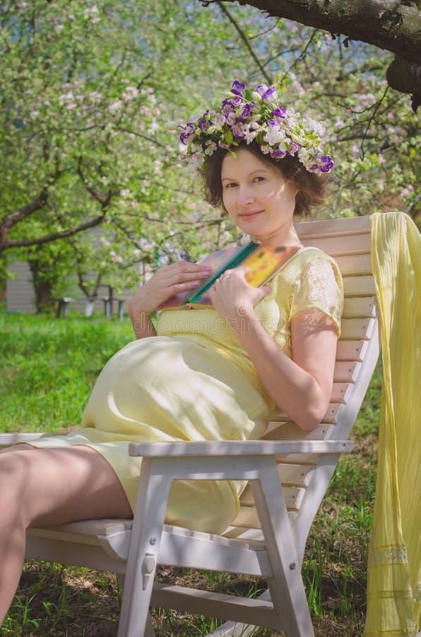 Όμορφη έγκυος γυναίκα σε ένα κίτρινο φόρεμα και ένα στεφάνι των λουλουδιών στοκ φωτογραφία