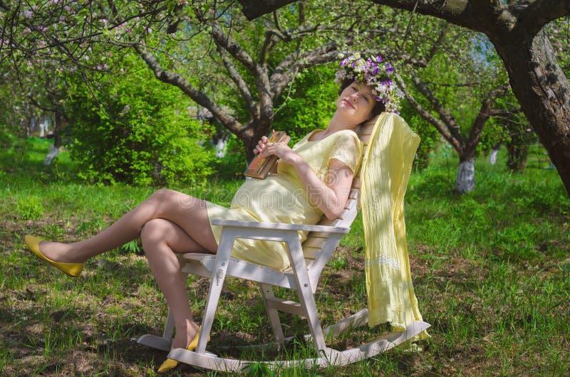 Όμορφη έγκυος γυναίκα σε ένα κίτρινο φόρεμα και ένα στεφάνι των λουλουδιών στοκ φωτογραφίες