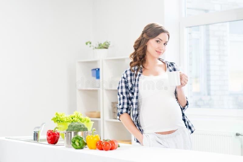 Όμορφη έγκυος γυναίκα στην κουζίνα με την τσάντα και το μήλο αγορών στοκ εικόνα