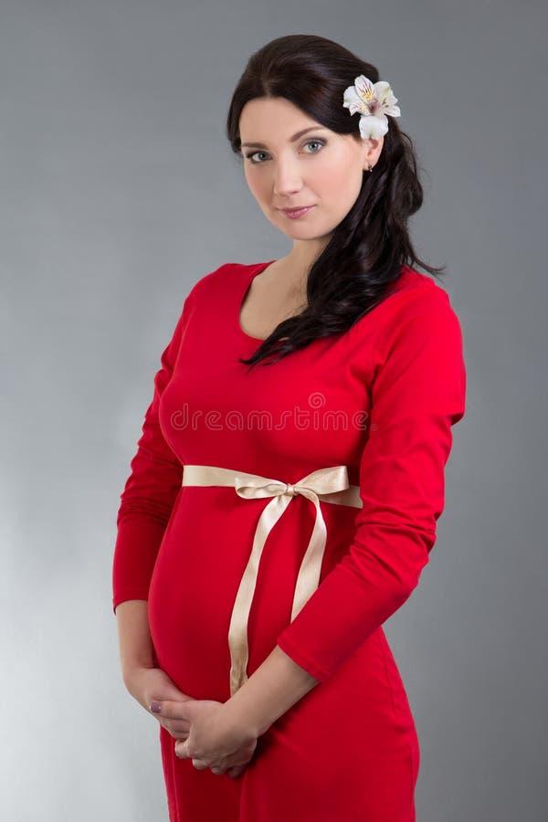 Όμορφη έγκυος γυναίκα στο κόκκινο φόρεμα πέρα από το γκρίζο υπόβαθρο στοκ φωτογραφία με δικαίωμα ελεύθερης χρήσης