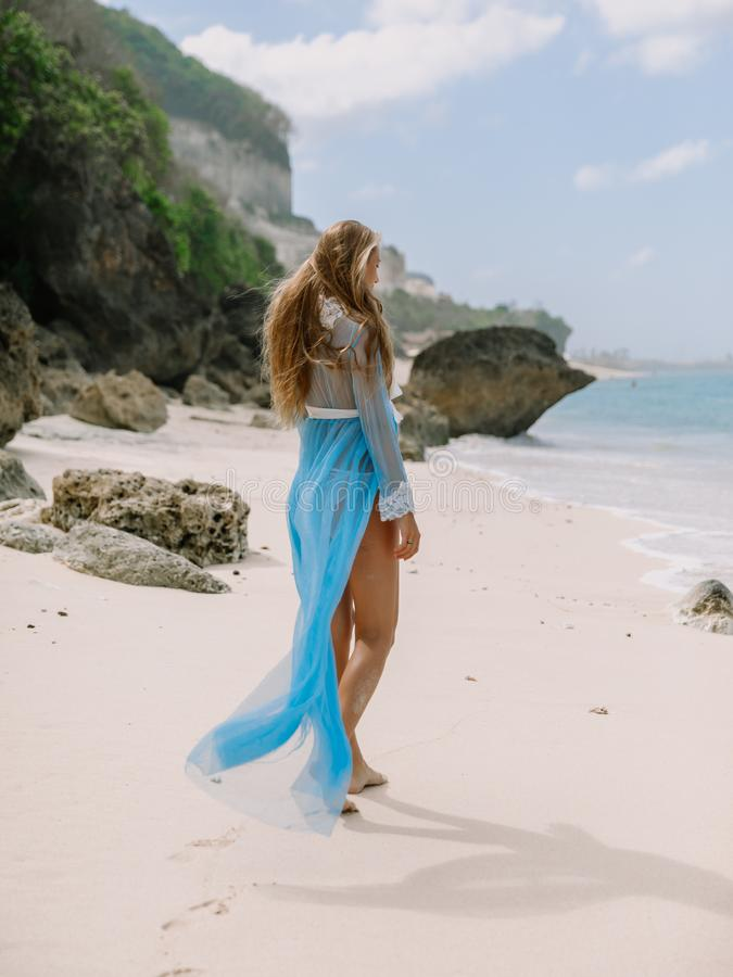 Όμορφη έγκυος γυναίκα στο φόρεμα μπουντουάρ που αναμένει το μωρό στην παραλία στοκ φωτογραφίες