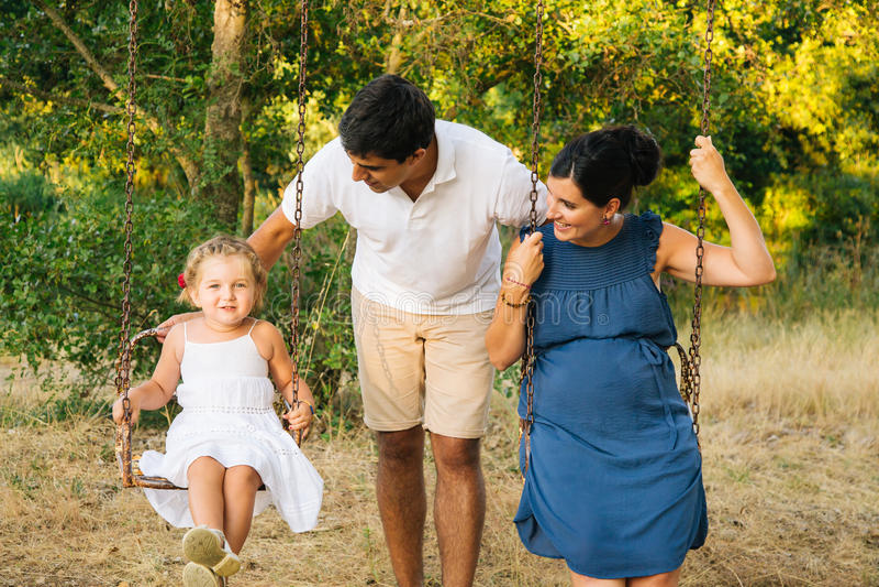 Όμορφη έγκυος οικογένεια στην ταλάντευση στοκ φωτογραφία με δικαίωμα ελεύθερης χρήσης