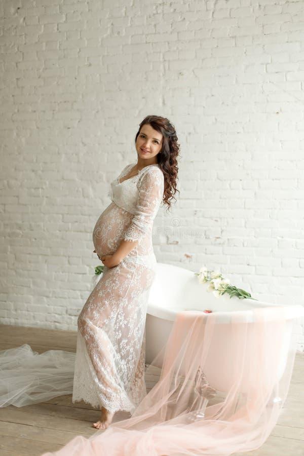 Όμορφη έγκυος παραμονή κοριτσιών κοντά σε μια μπανιέρα με το γάλα και τα λουλούδια και τα βλέμματα έξω το παράθυρο στοκ φωτογραφίες με δικαίωμα ελεύθερης χρήσης