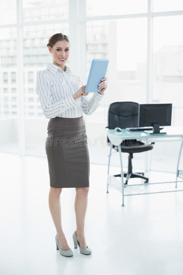 Όμορφη ήρεμη επιχειρηματίας που κρατά την ταμπλέτα της στεμένος στο γραφείο της στοκ φωτογραφία