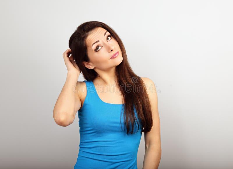 Όμορφη αβέβαιη σοβαρή γυναίκα με το δάχτυλο κάτω από το πρόσωπο που σκέφτεται και ανατρέχοντας στο περιστασιακό πουκάμισο και μακ στοκ εικόνες