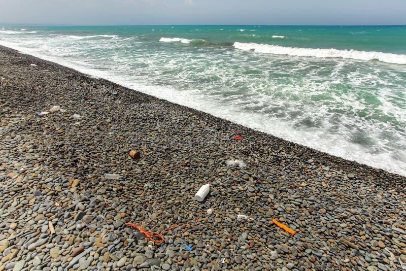 Όμορφη αβλαβής σκοτεινή παραλία πετρών χαλικιών με τα απορρίματα, συνήθως πλαστικός, που πλένονται έξω Ωκεάνια έννοια ρύπανσης στοκ φωτογραφία με δικαίωμα ελεύθερης χρήσης