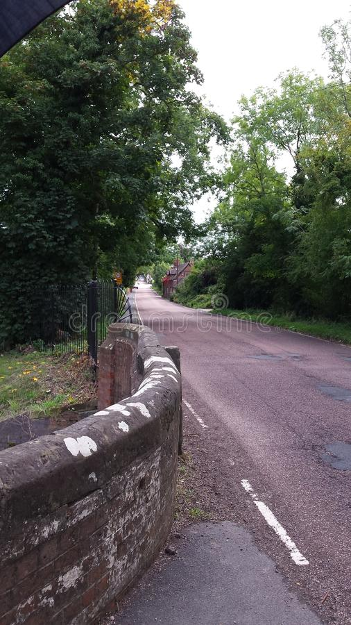 Όμορφη αγγλική πάροδος επαρχίας με τον τοίχο πετρών και τα πράσινα δέντρα στοκ φωτογραφία