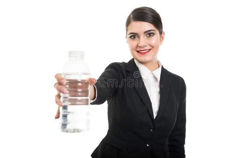Όμορφη αεροσυνοδός που προσφέρει το μπουκάλι νερό και το χαμόγελο στοκ εικόνες με δικαίωμα ελεύθερης χρήσης