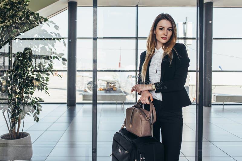 Όμορφη αεροσυνοδός που στέκεται στη στολή της με τις τσάντες της έτοιμες για μια πτήση στοκ φωτογραφία