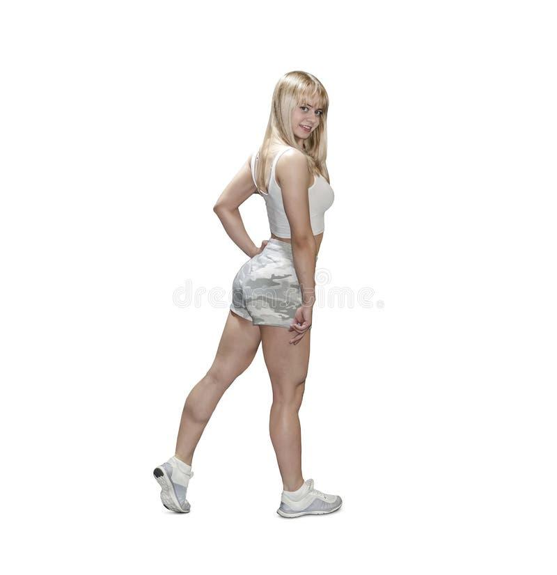 Όμορφη αθλητική τοποθέτηση κοριτσιών που απομονώνεται πέρα από το άσπρο υπόβαθρο Ξανθό bodybuilder στα κοντά στρατιωτικά σορτς κα στοκ εικόνες