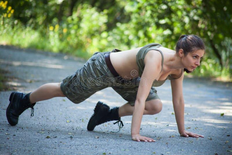 Όμορφη αθλήτρια που εκπαιδεύει το ώθηση-UPS στο πάρκο στοκ φωτογραφία με δικαίωμα ελεύθερης χρήσης