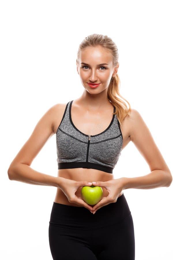Όμορφη αθλητική τοποθέτηση κοριτσιών, που κρατά το μήλο πέρα από το άσπρο υπόβαθρο στοκ εικόνες